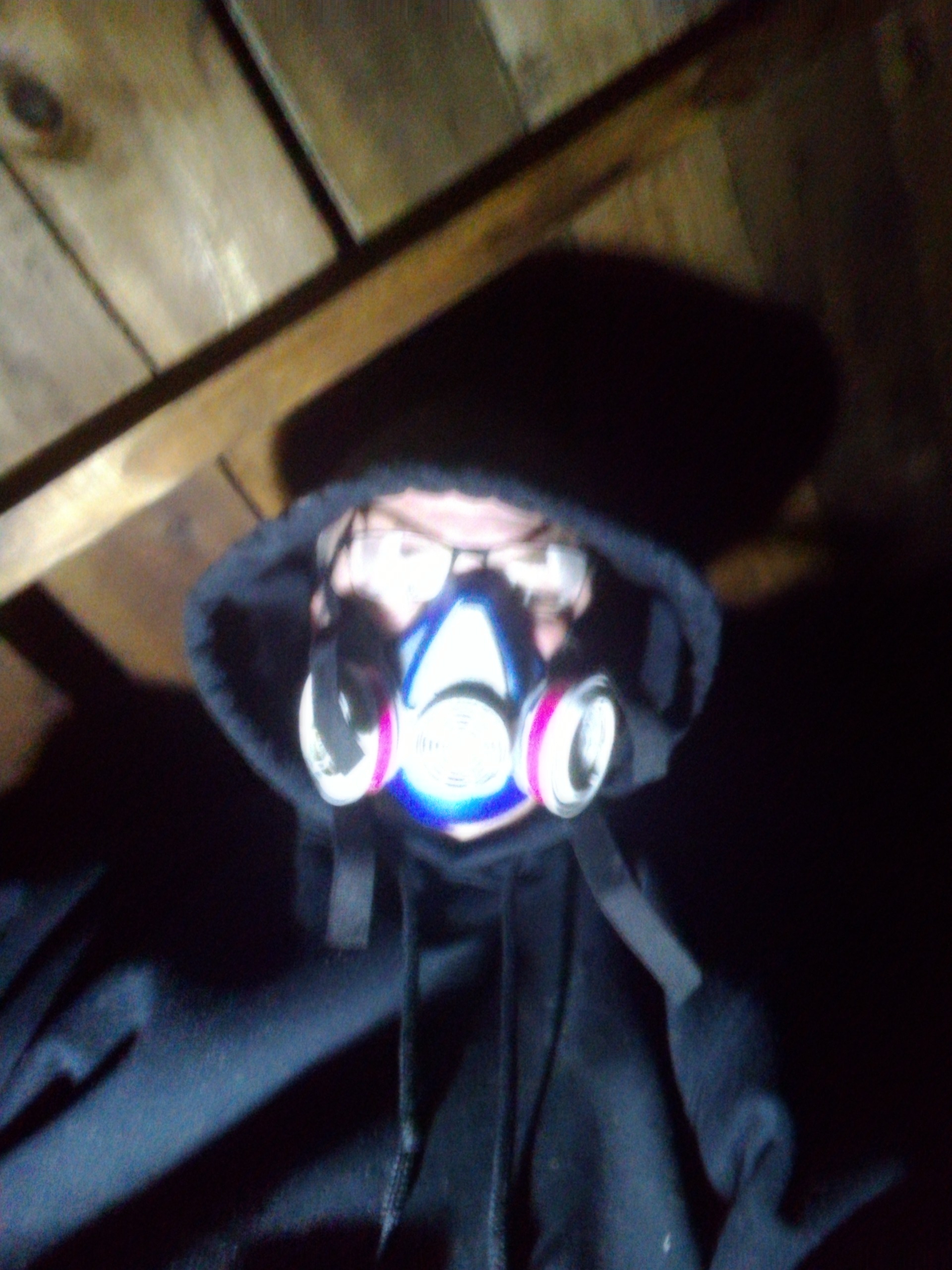 A blurry selfie of me hearing a black hooded sweatshirt and a dust mask while working in the attic. Planks for the rook are just behind me.