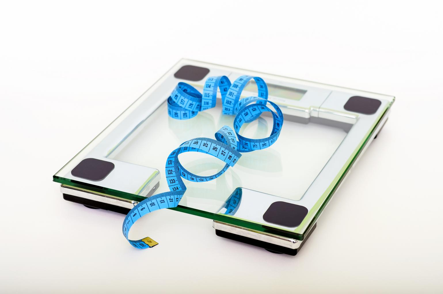 A tape measure on a scale ot demonstrate weight loss