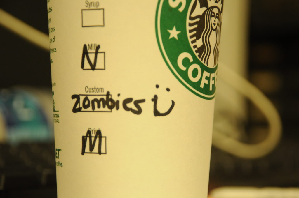 A paper Starbucks cup with Zombies written on it.