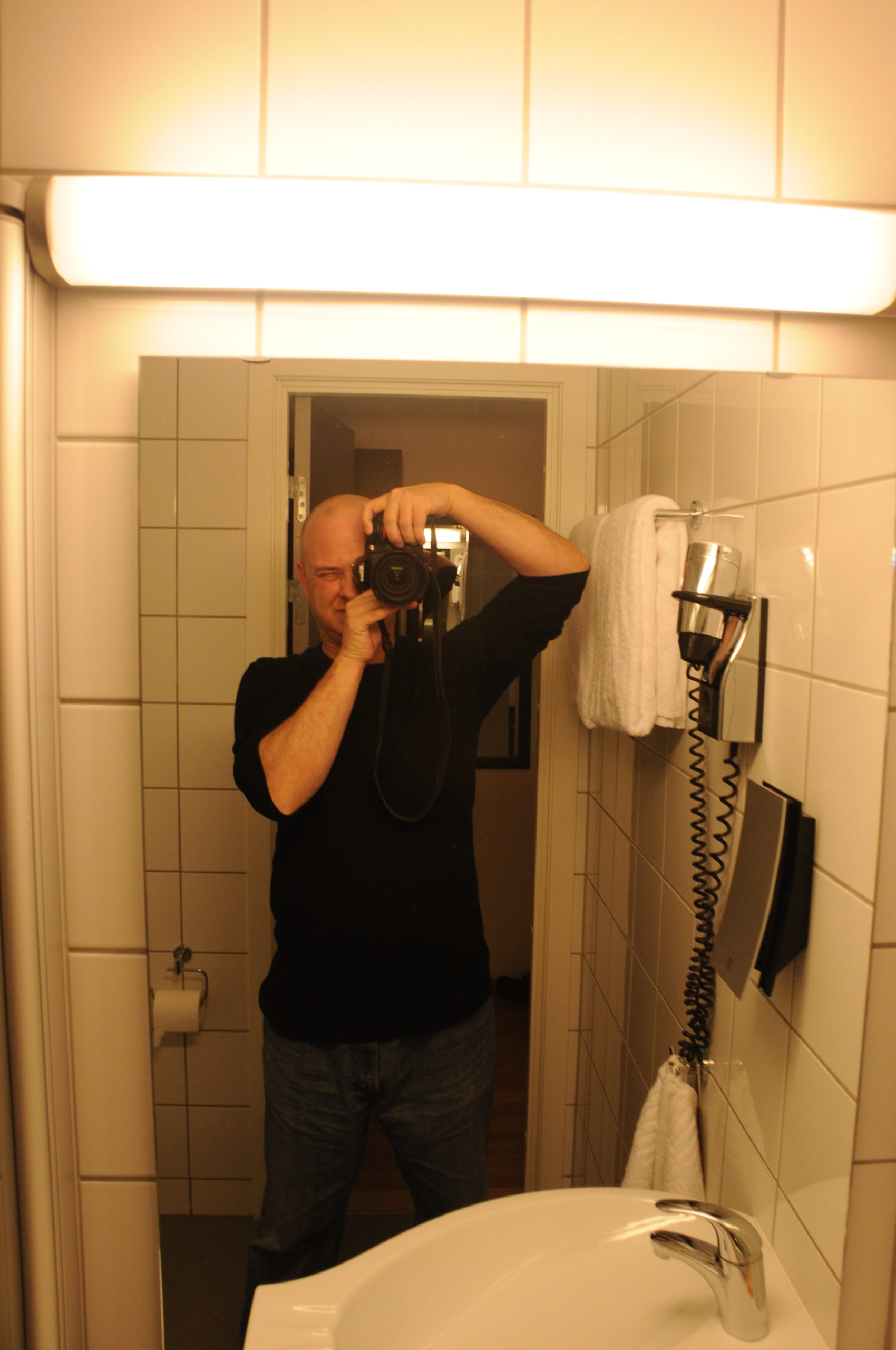 I used a Nikon D300 SLR camera to take a selfie in the mirror in the hotel room in Tromsø. I'm wearing jeans and a long sleeve black t-shirt.