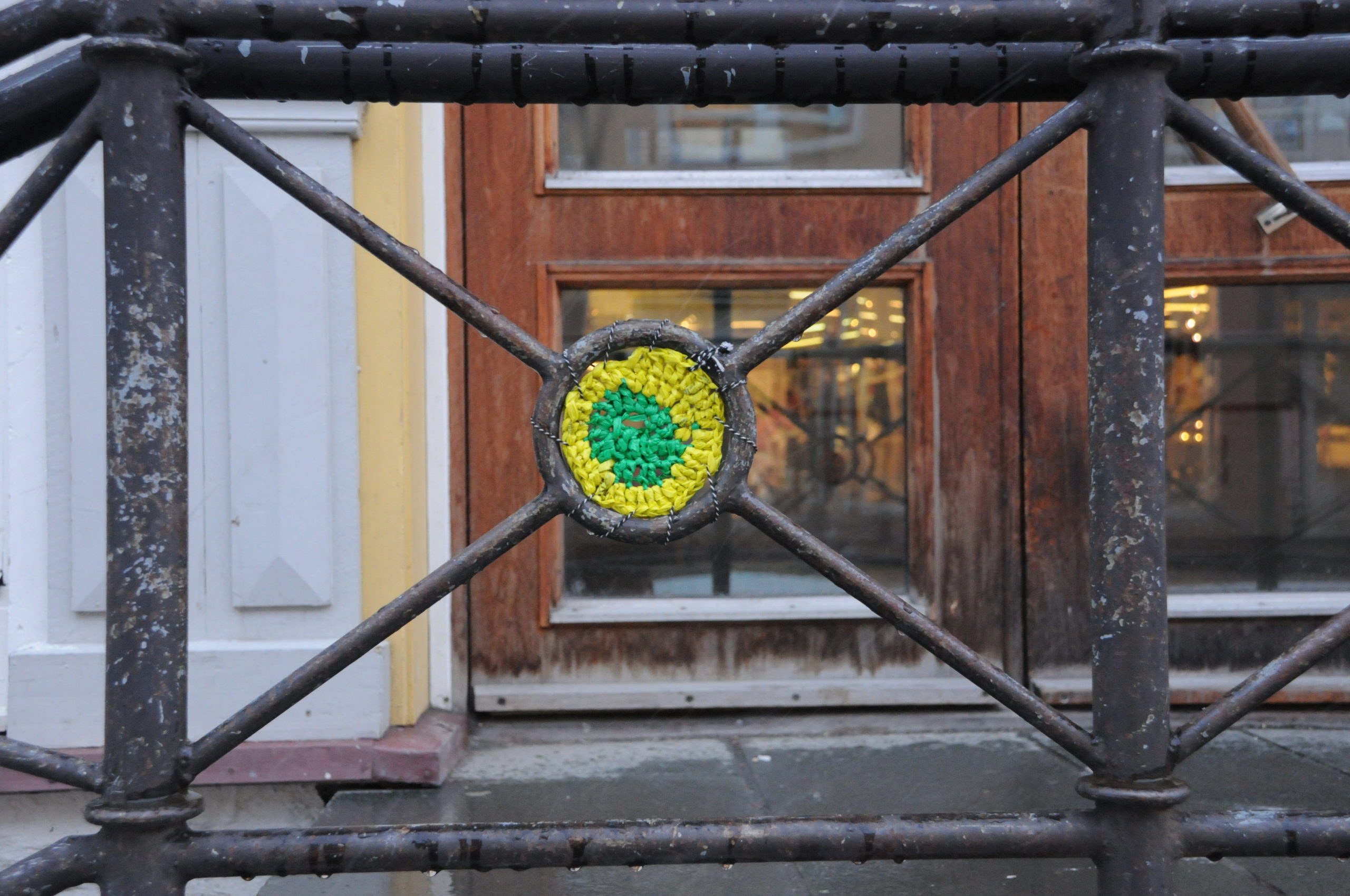 A piece of yellow and green crochet is set into a metal railing. In the background is a wooden door that leads into the building.