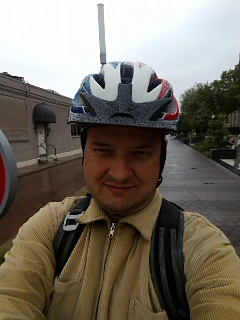 I'm wearing a green corduroy jacket, a backpack, and a rain-spattered bicycle helmet. In the background is a building, some trees, and the brick-paved trail.
