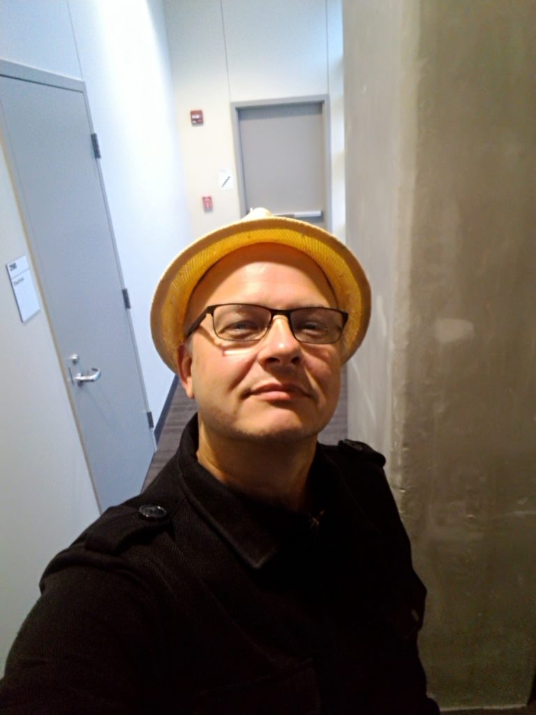 In the photo I'm wearing a black cotton peacoat, black metal frame eyeglasses and a straw hat. In the background is a concrete pillar, a couple of walls, and two metal doors.
