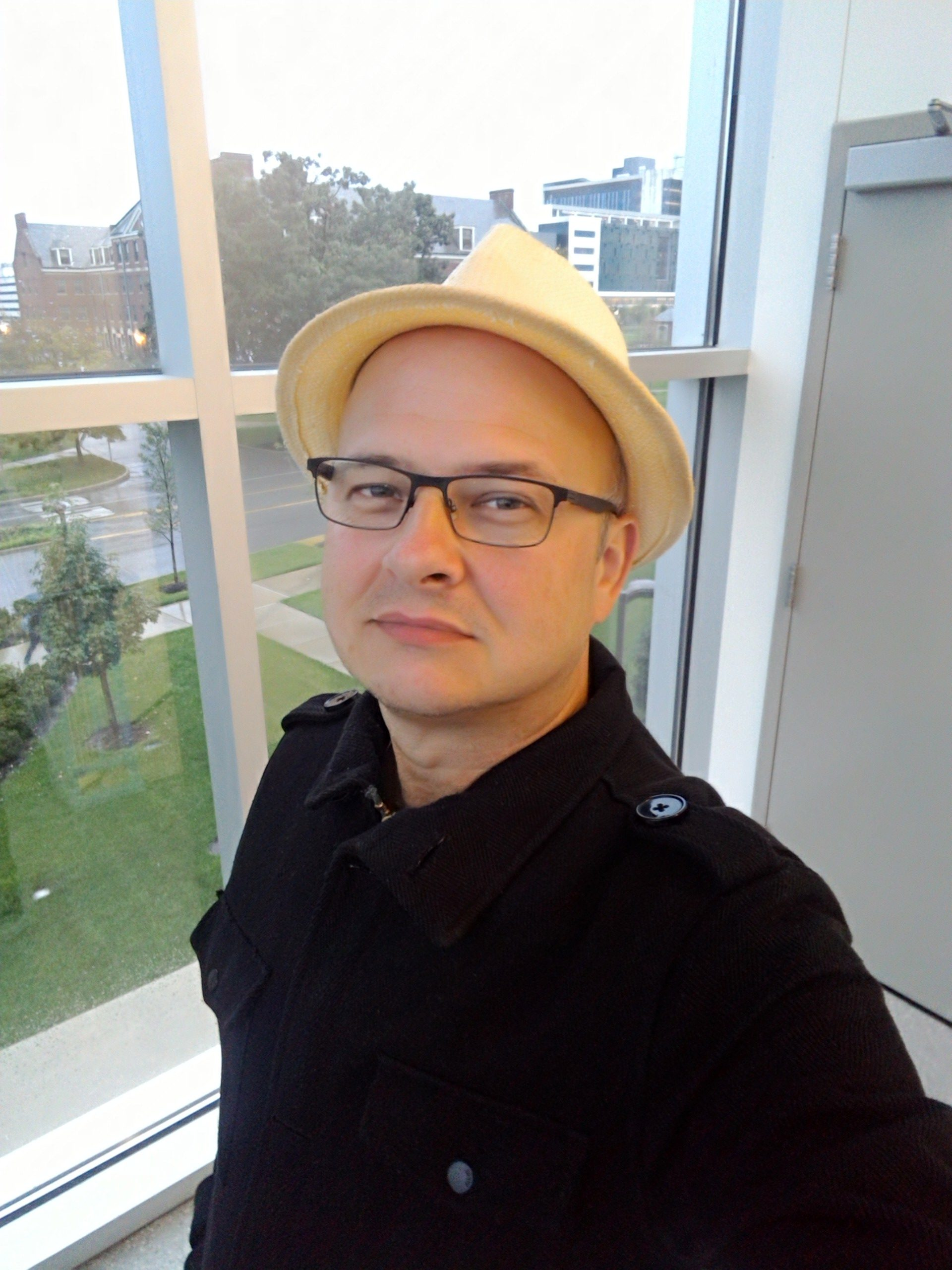 I'm wearing a black cotton peacoat black metal-framed eyeglasses, and a straw fedora. In the backgrounds is a metal door and large windows through which a lawn and other buildings can bee seen.