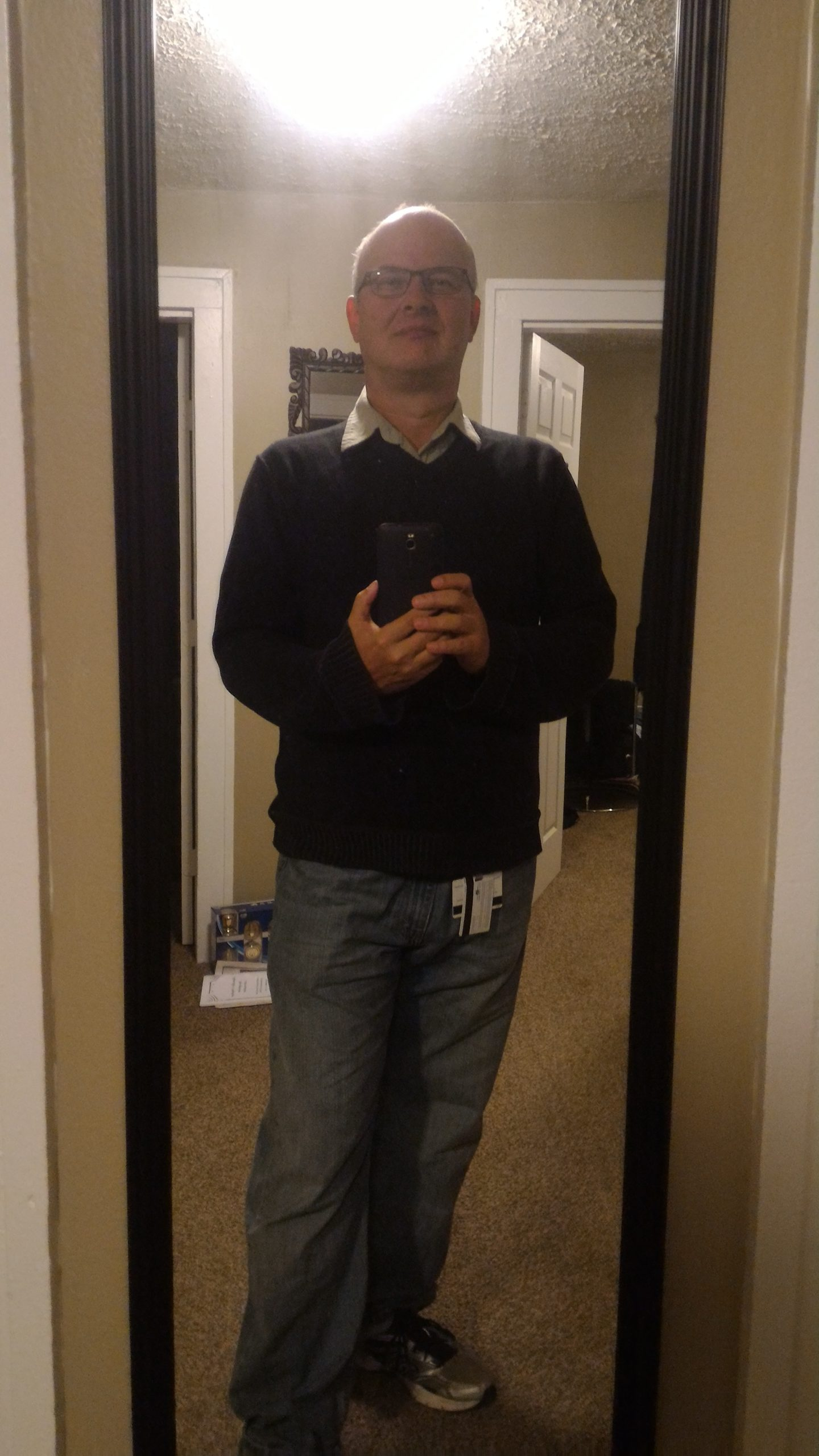 This photo shows me wearing running shoes, baggy jeans, and a black sweater over a collared shirt. An ID badge hangs from my belt and is visible just below the hem of the sweateer. Thebackground shows the black frame of the mirror against a beige wall.