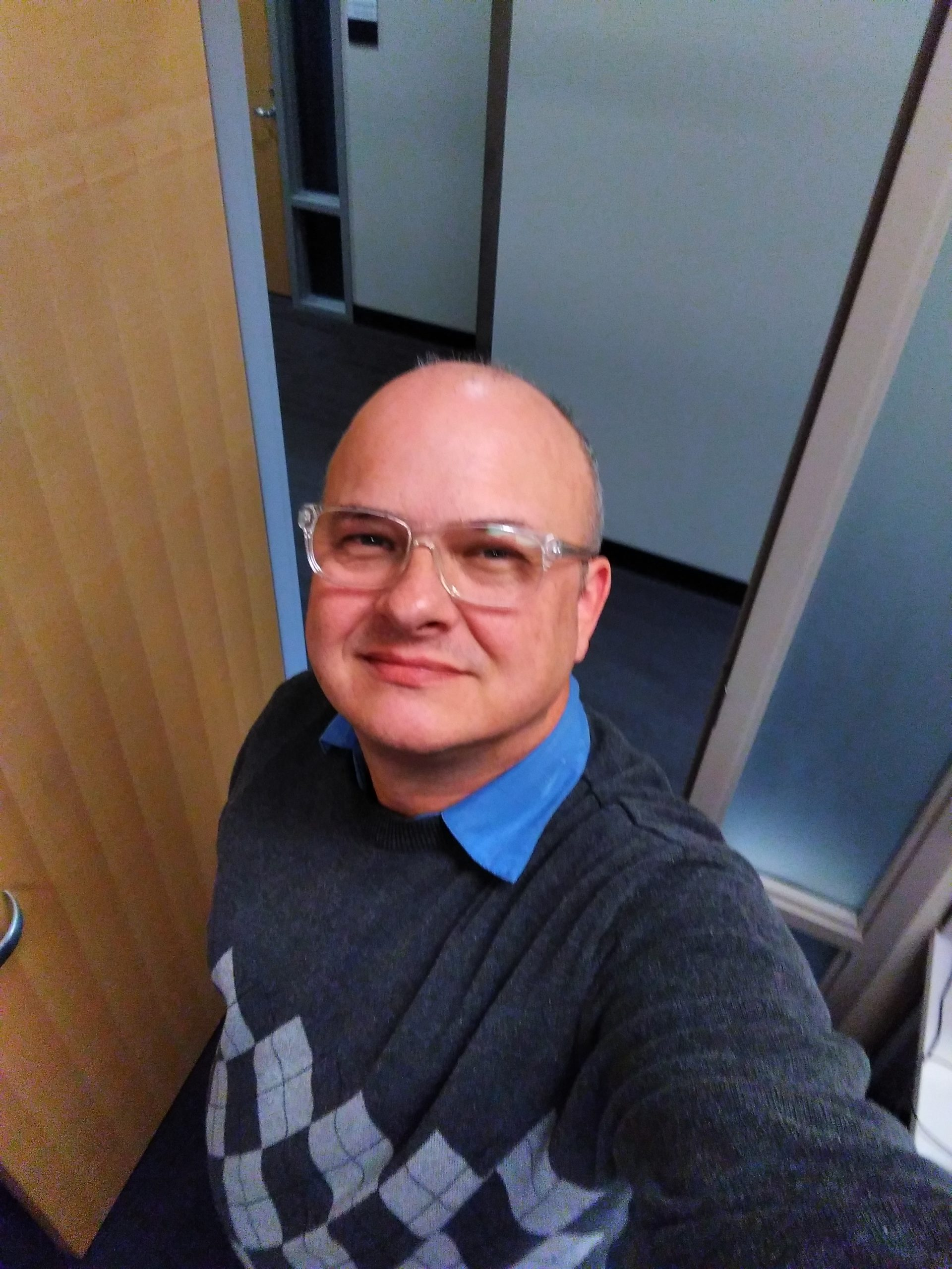 In the photo, I'm wearing a grey Argyle sweater over a blue-collared shirt My face is clean shave and adorned with clear-framed eyeglasses. Behind me is an open door and wall on the other side of the hallway. a wall .