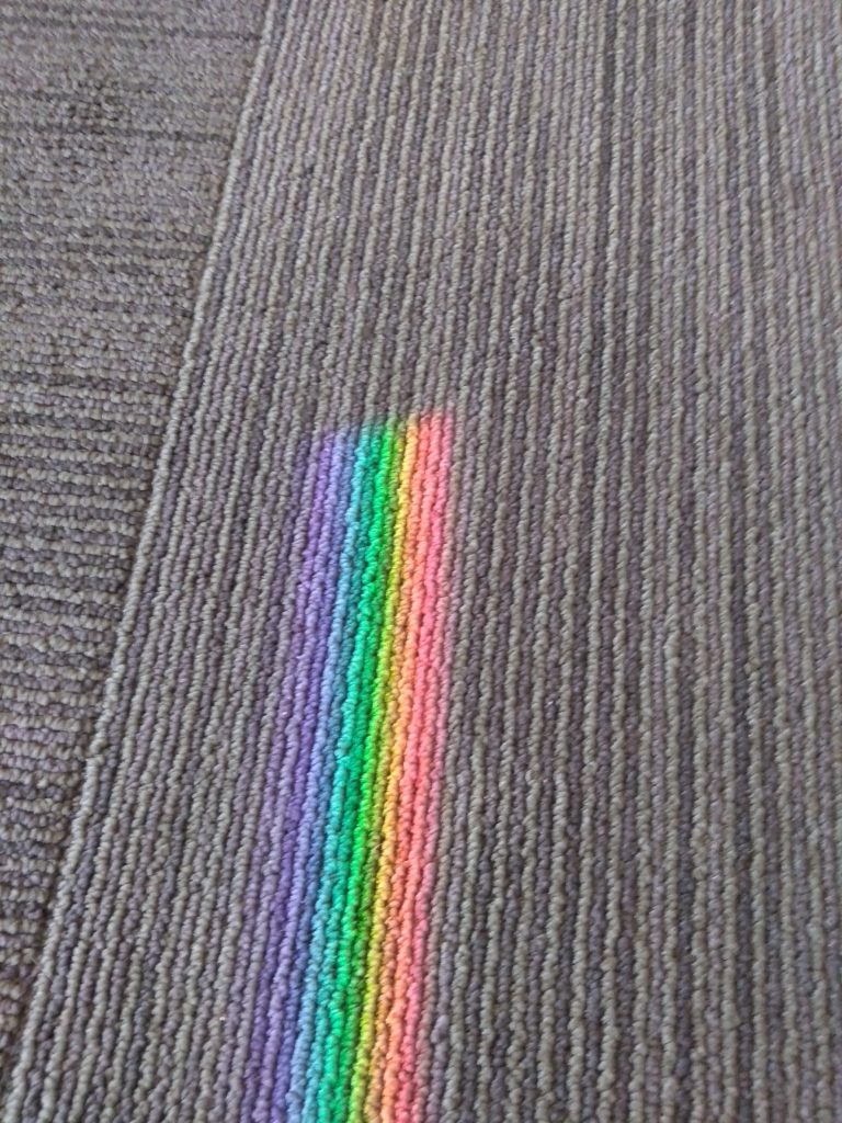 A rainbow stops on a patch of carpet.