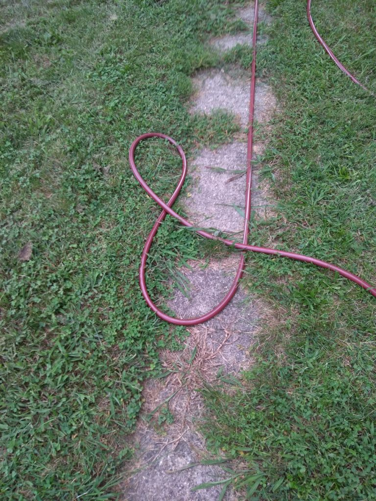 A garden hose takes the form of an ampersand in the grass.