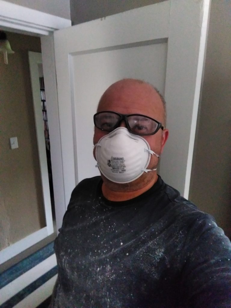 I'm wearing a dark shirt covered in plaster dust, an N95 face mask, and safety glasses. In the backgrounds is an open wodden door and the beige painted walls of the hallway..