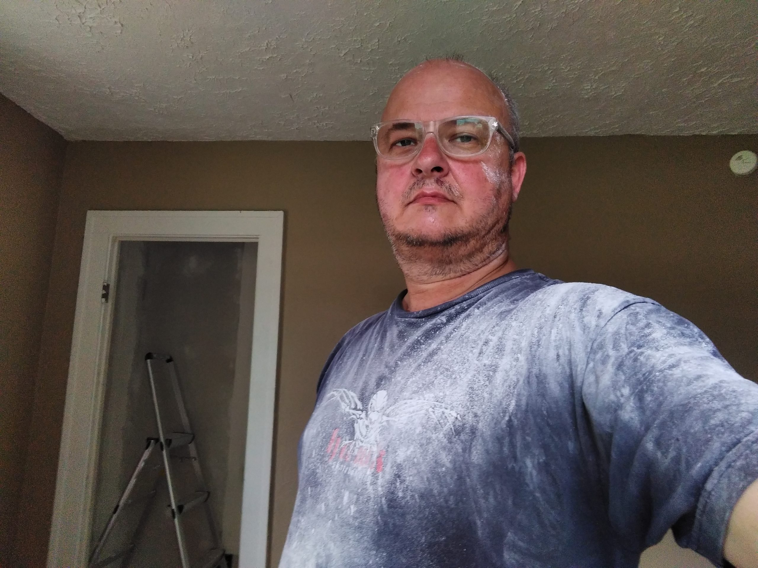 I', wearing a navy blue t-shirt covered in plaster dust, and clear-framed eyeglasses. My face diplays a mixture of stubble and plaster dust. The background shows the wall of the kitche and the doorway of the pantry.