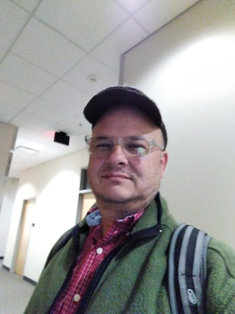 In this photo I'm wearing a green fleece jacket, a backpack, a red-checked collared shirt, clear-framed eyeglasses, and a well-worn baseball cap. In the background is the hallway with its beige-painted walls.