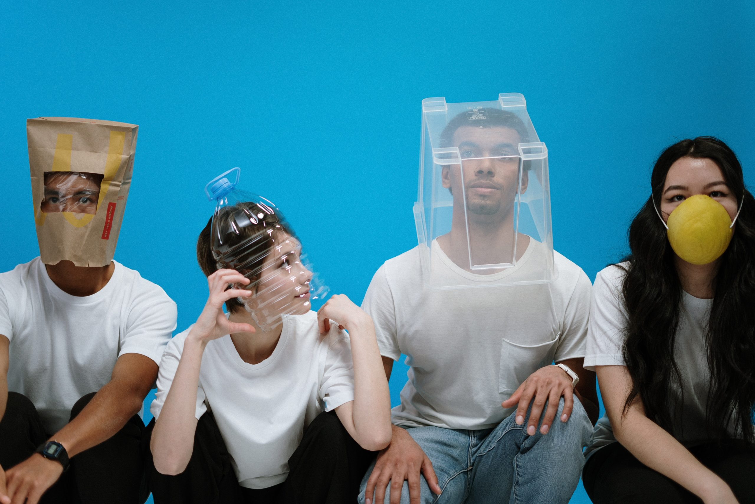 Four people wearing face masks made from unusual items.
