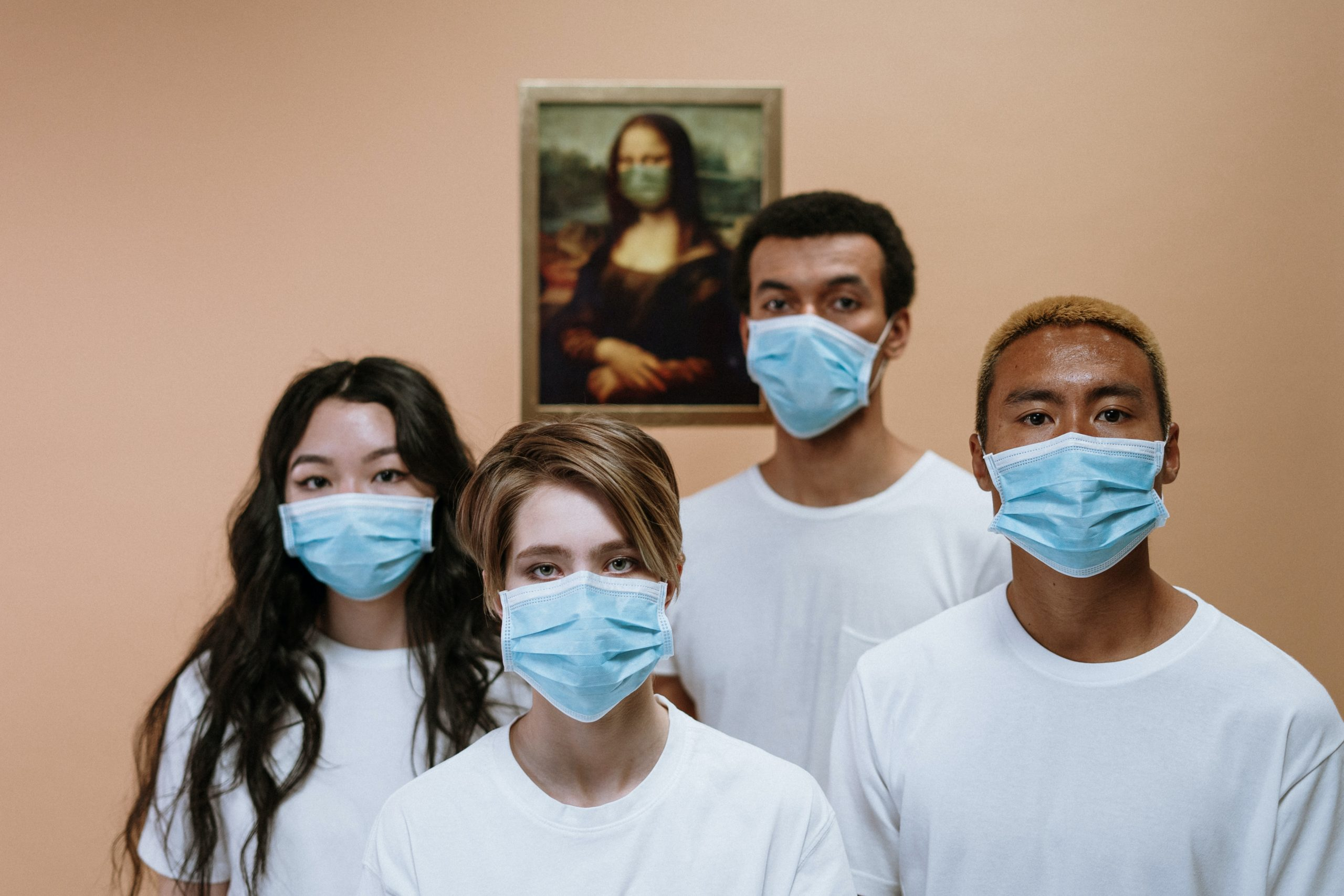 Four people wearing surgical masks while standing in fron of the Mona Lisa that is also wearing a mask.