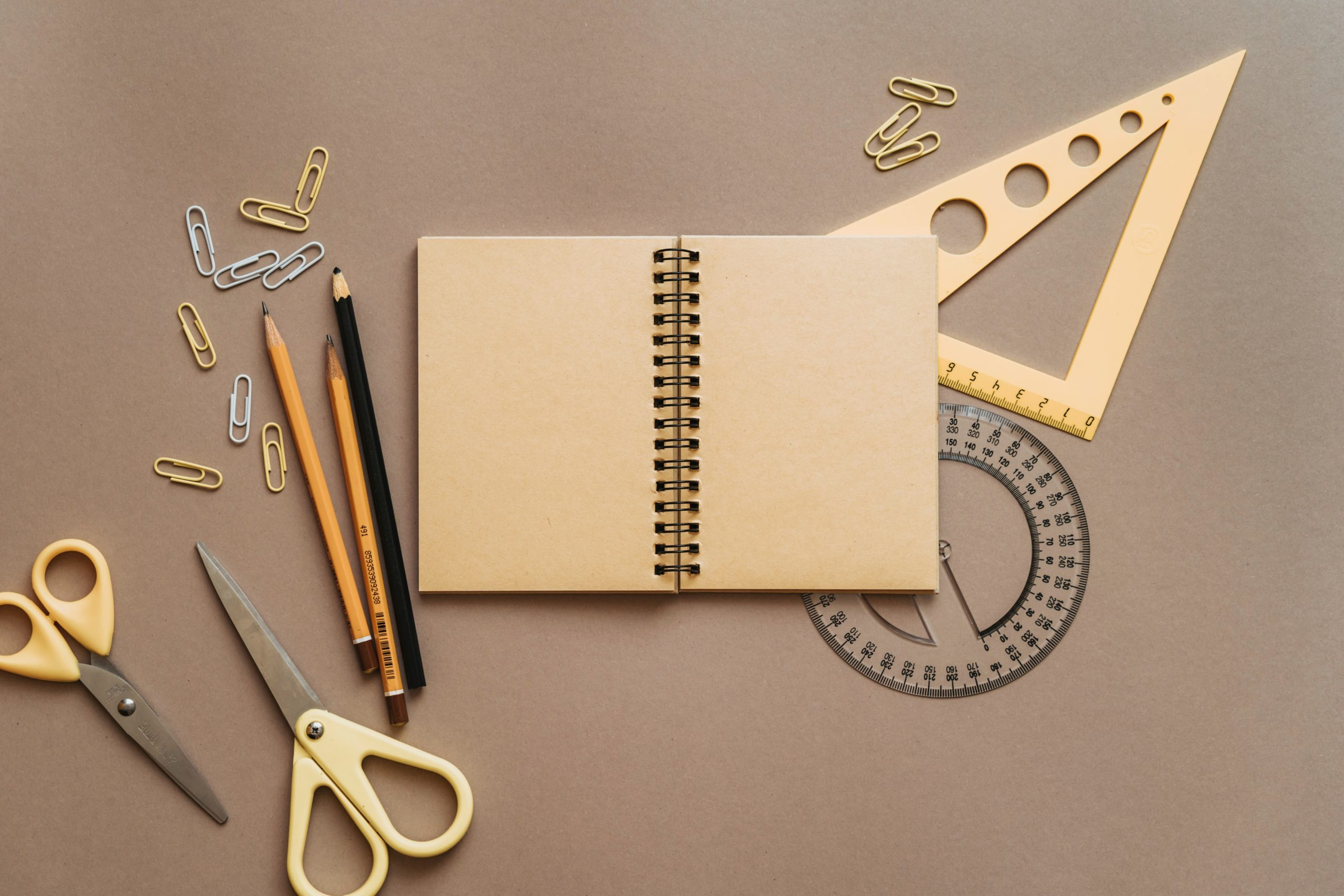 A desktop with scissors, pencils, paperclips, a notebook, a protractor, and a plastic triangle