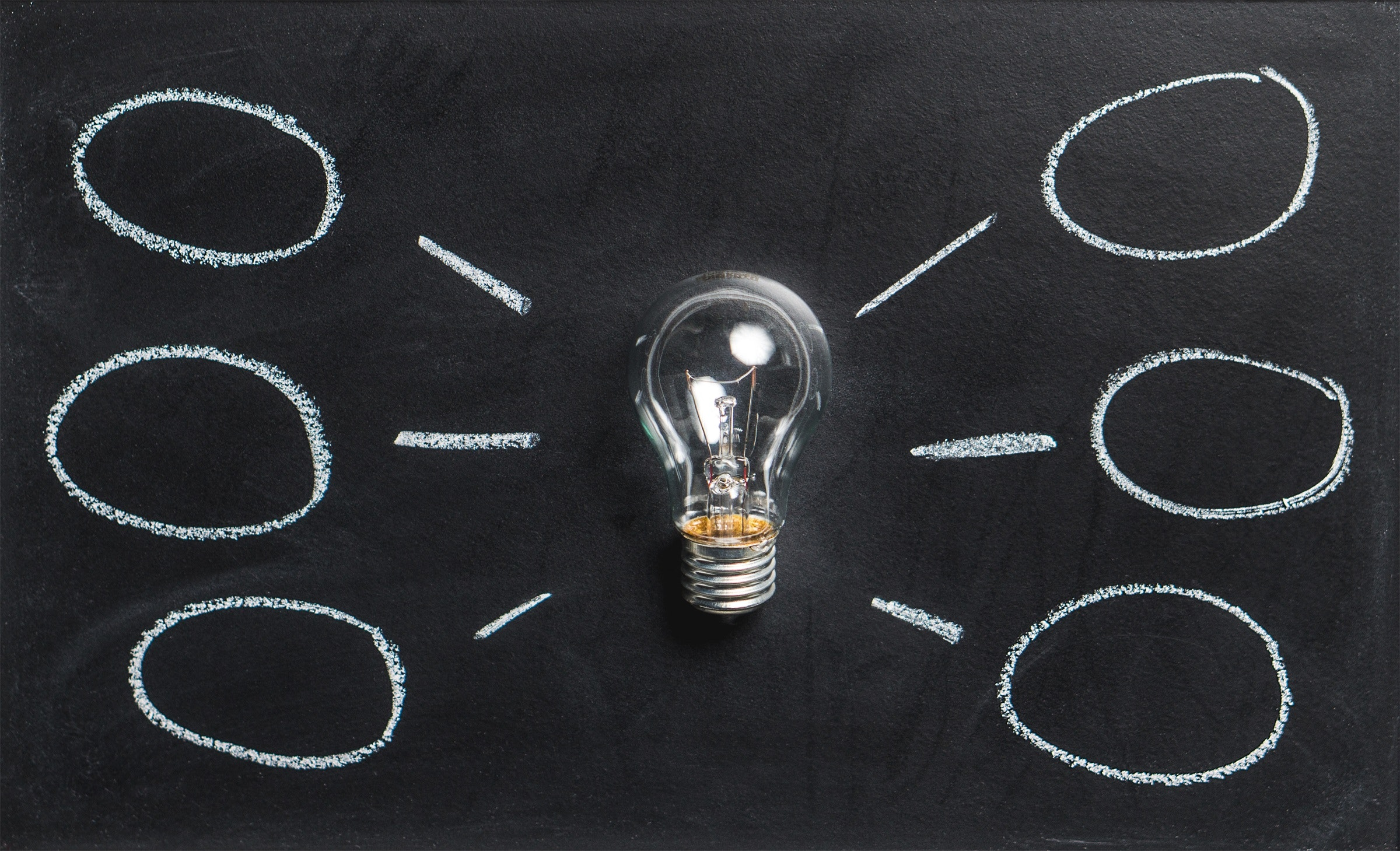 A clear light bulb on a blackboard surrounded by thought bubbles drawn in chalk.