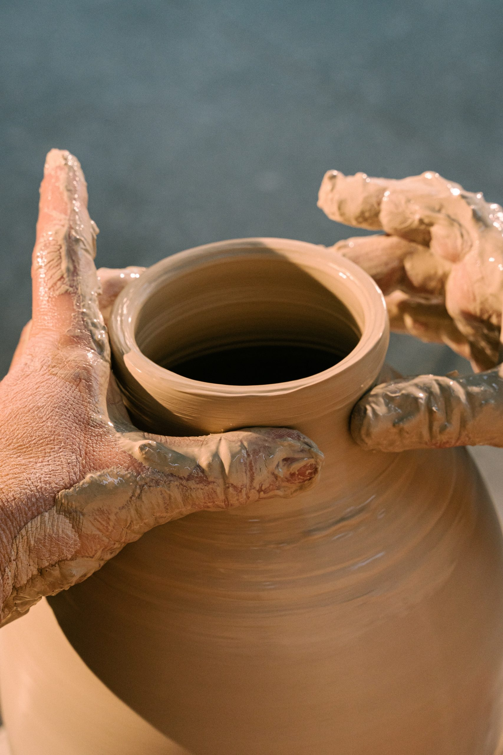 A pair of muddy hands is working a clay pot on a potting wheel