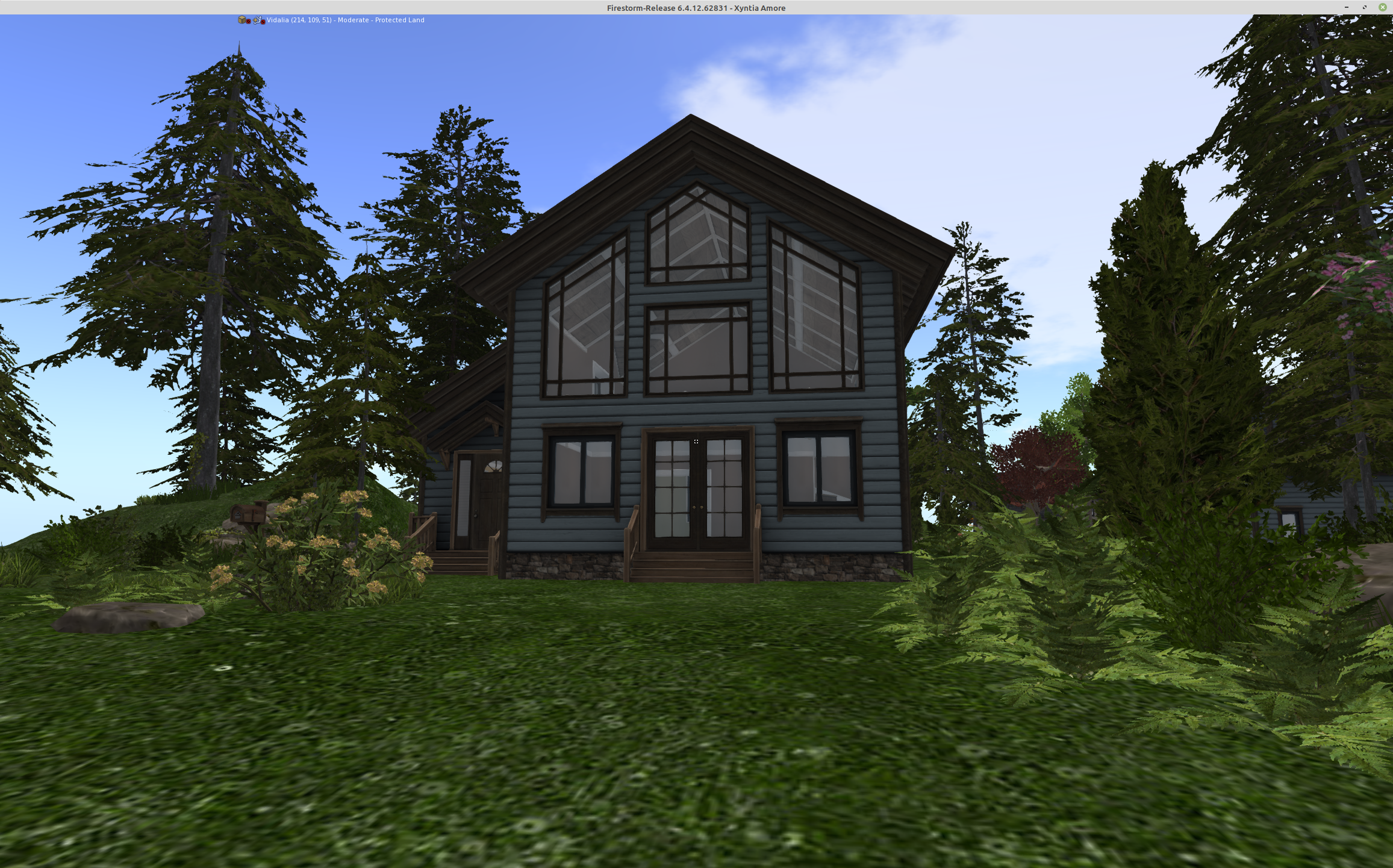 A screenshot of my new home in Second Life. It is a two-story home with lots of windows and is surrounded by lots of trees and bushes.