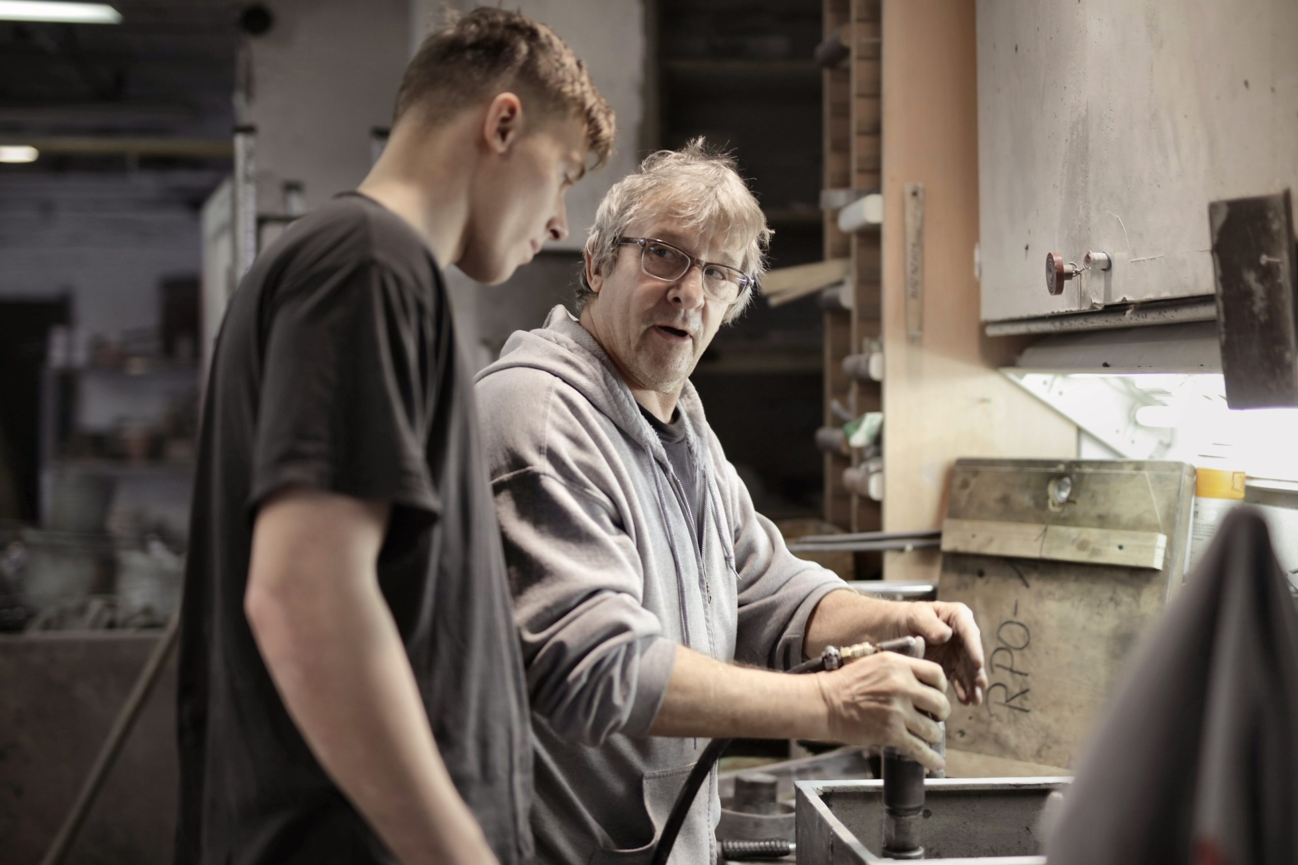 An older man is controlling a mechanism as an apprentice watches.