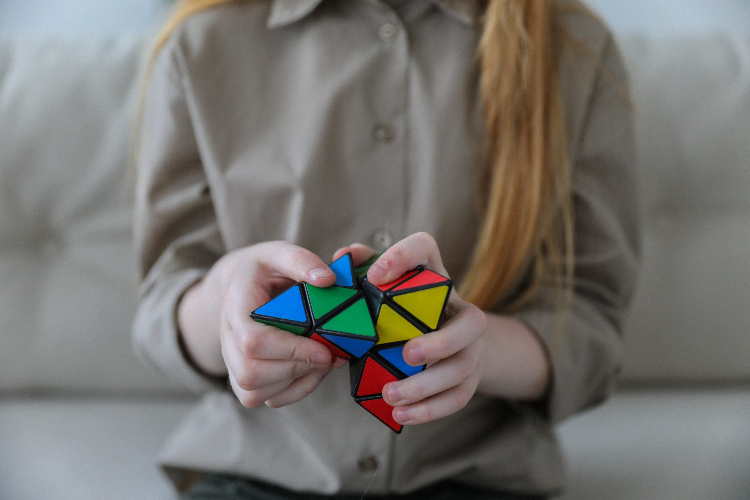 A girl is holding a brightly colored Rubik's pyramid puzzle in her hands.