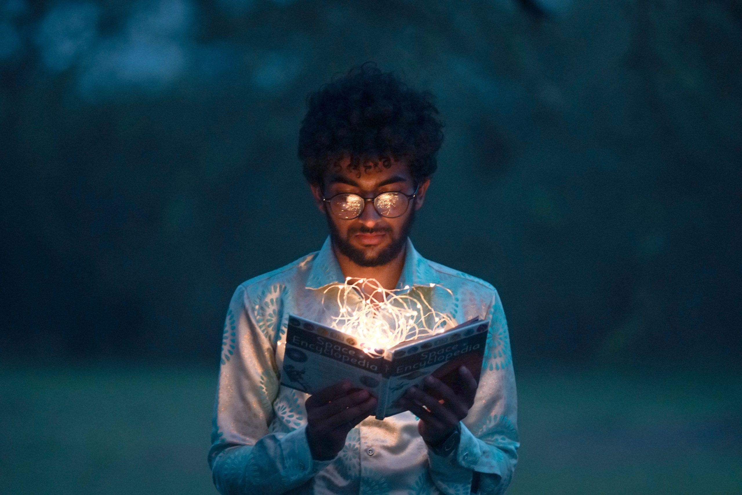 A man is outdoors and is holding a book open in front of him. The book is glowing, as if the contents are illuminating.