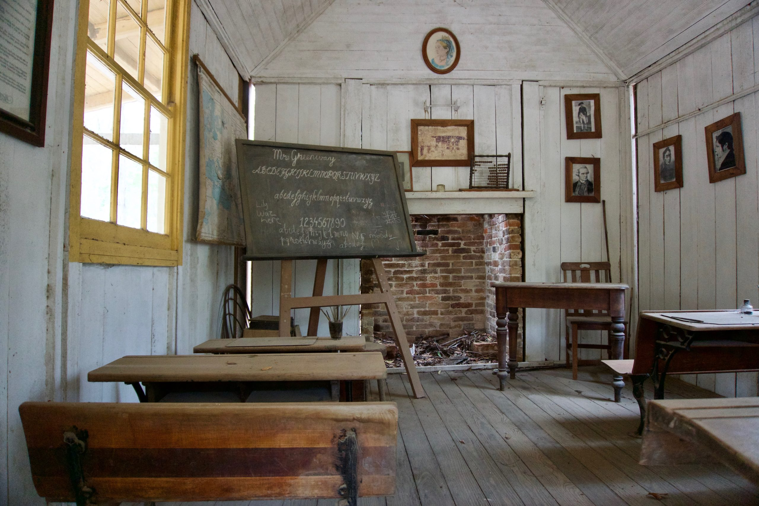 A very old classroom with wooden desks, a brick fireplace, and a blackboard on an easel. On the blackboard is the English alphabet written in cursive.