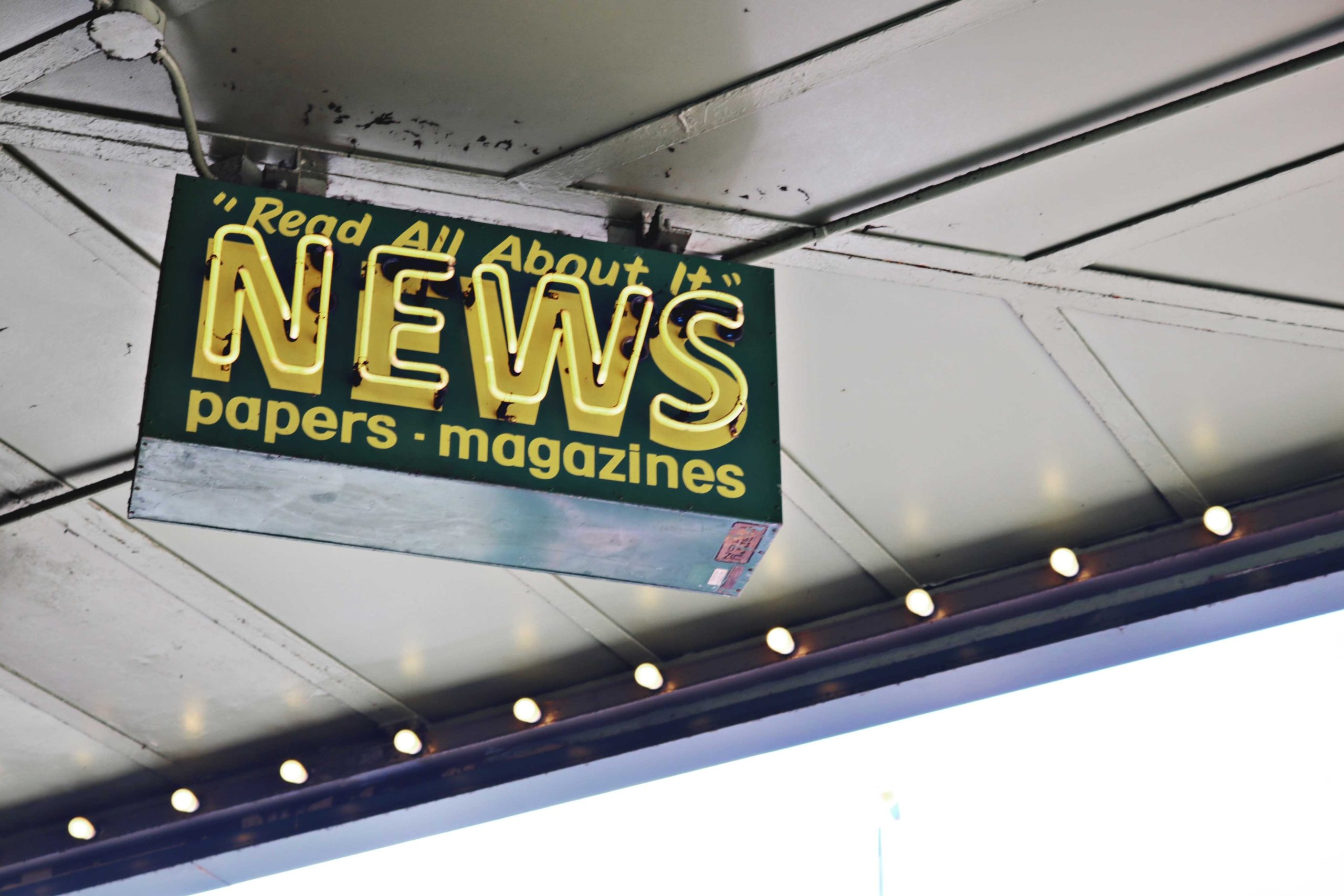 "A neon sign mounted on a building reads ""Read All About It. News. Papers. Magazines."""