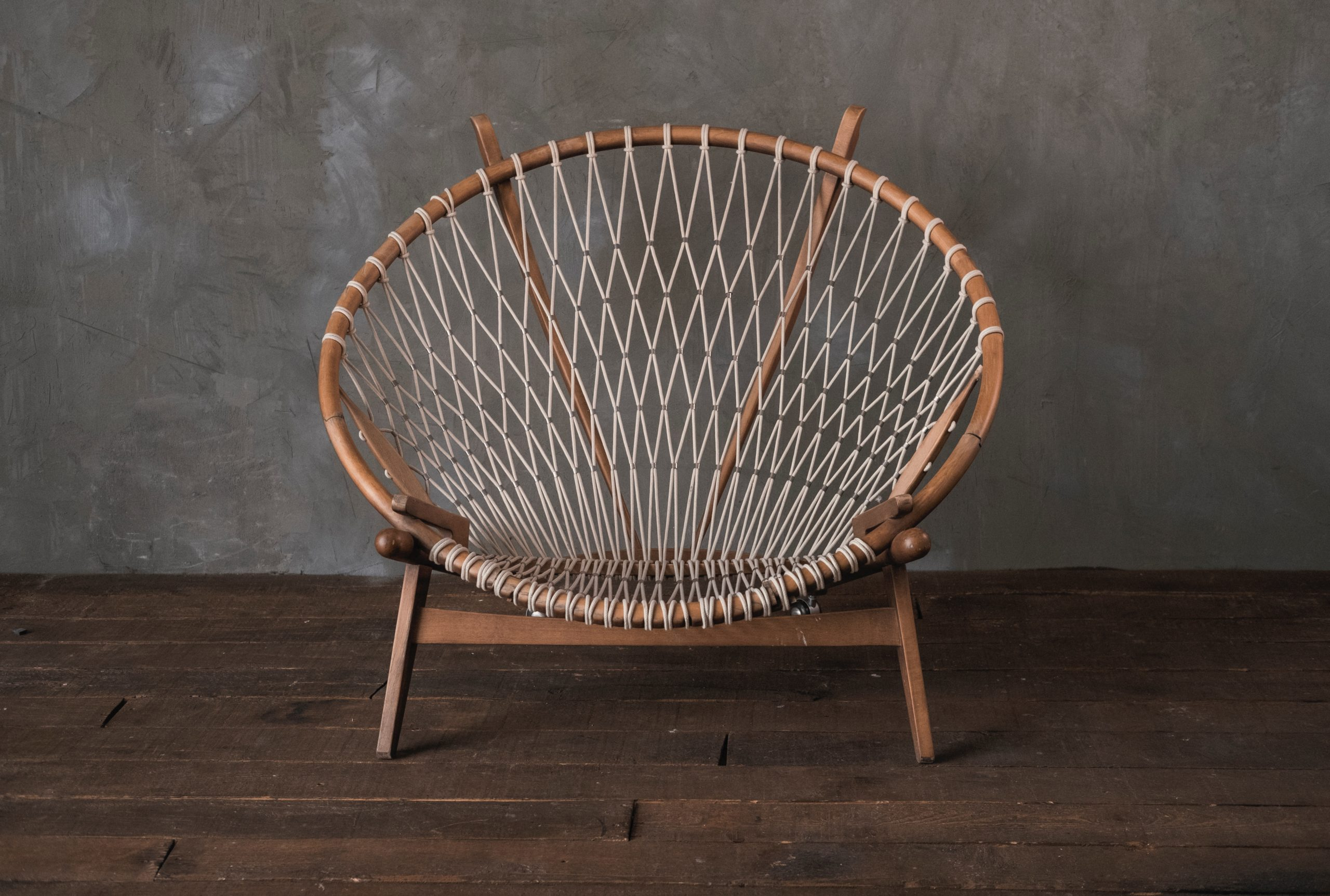 A chair with a wood frame and a rope seat