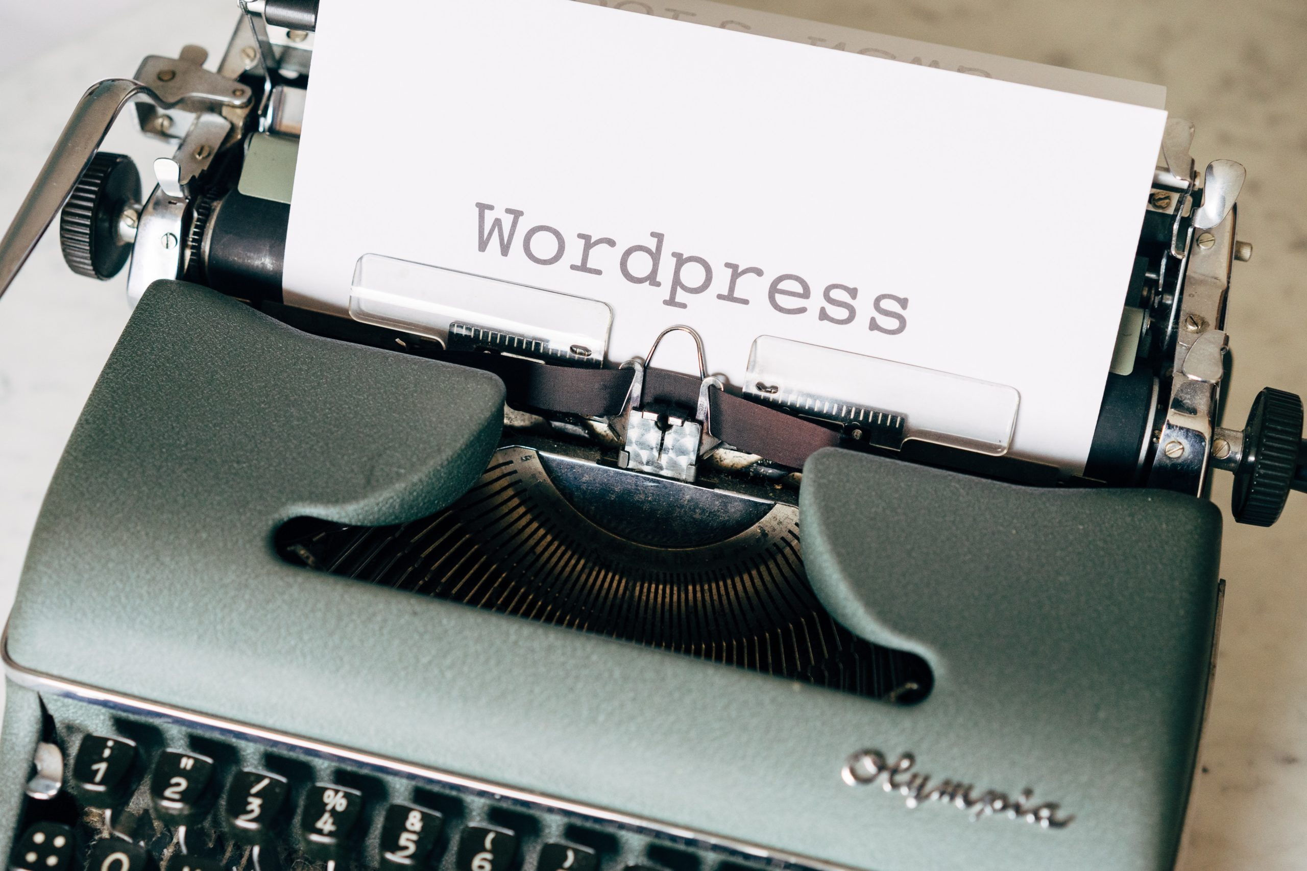 A typewriter with a sheet of paper in it, upon which is the word WordPress.