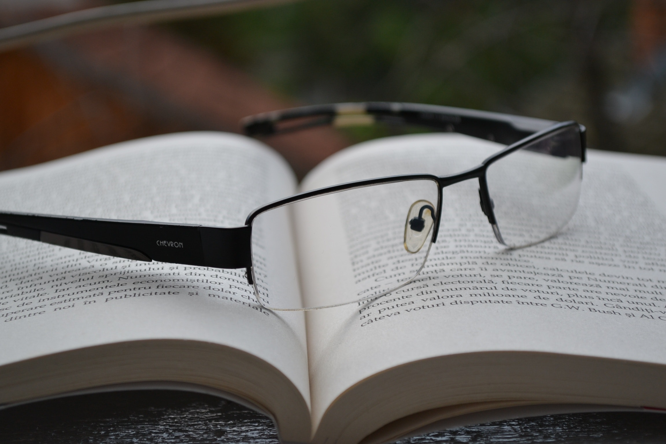 A pair of reading glasses is laid upon an open book.